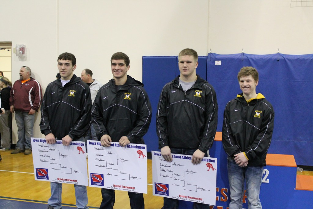Wrestlers posing with tournament posters
